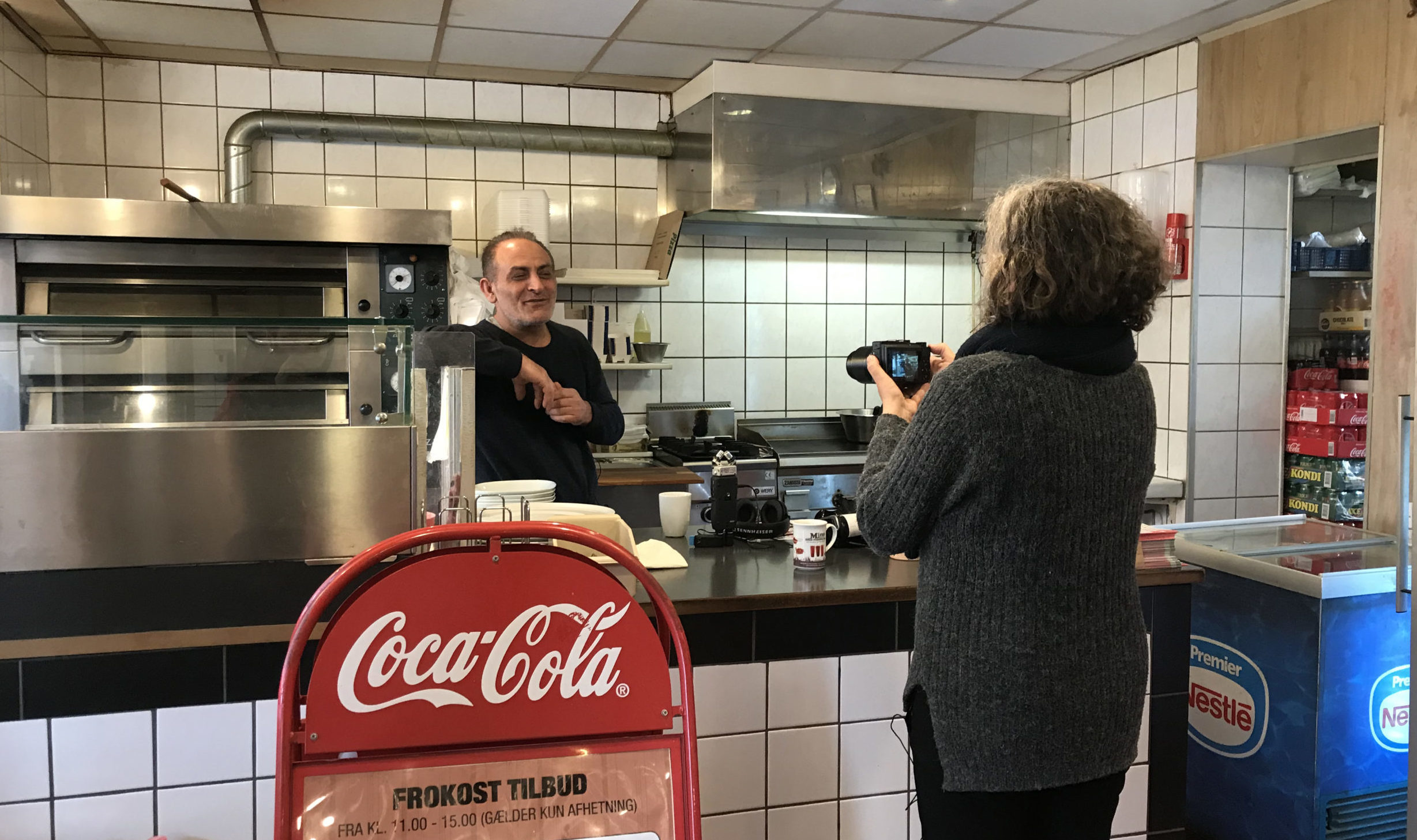 Kvinde filmer mand i pizzaria, hans arbejdsplads