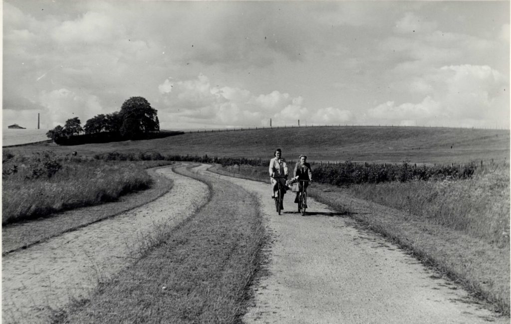 Two women on bikes in a park.