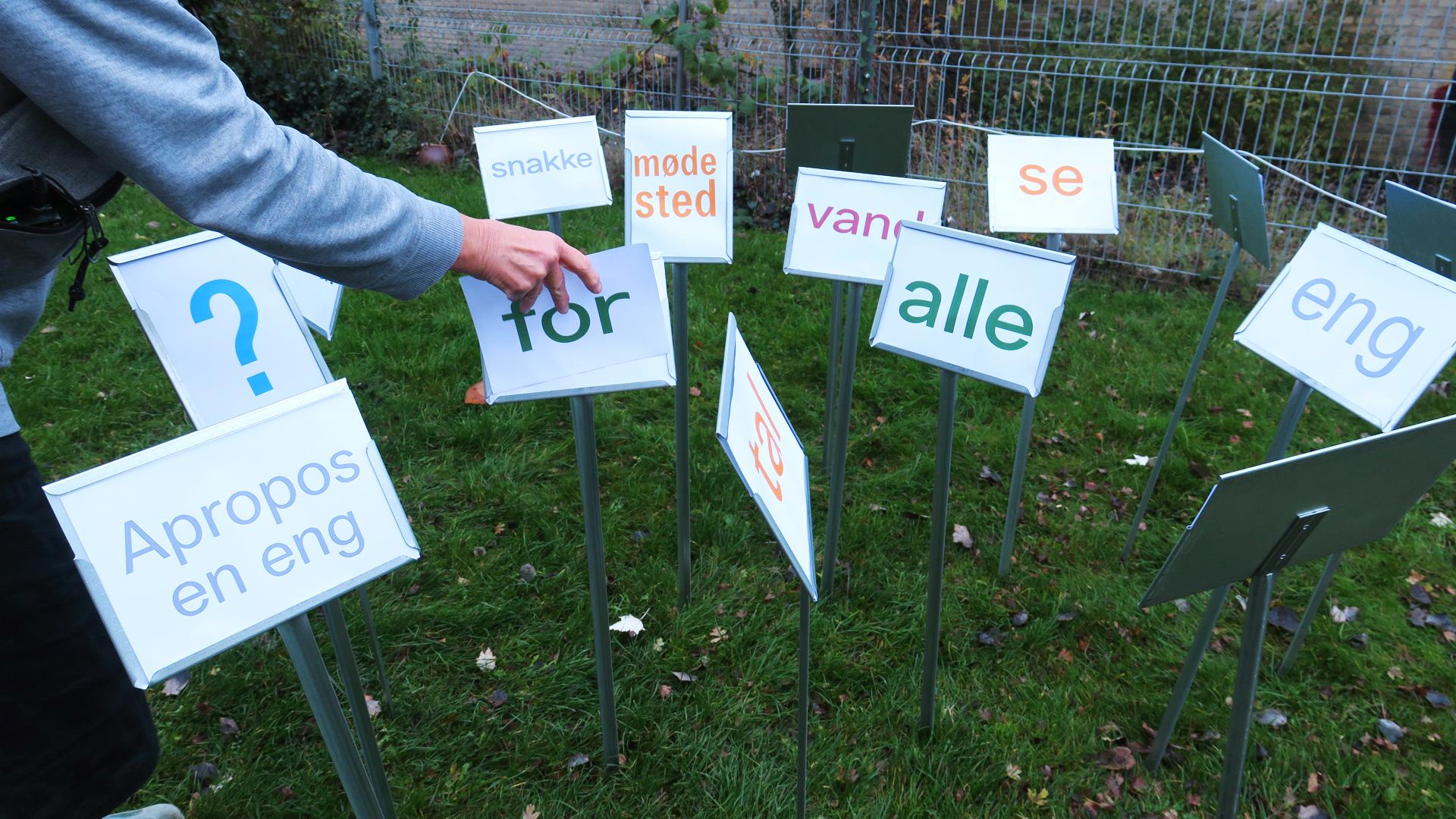En hånd placerer et skilt på en græsplæne ved siden af mange andre skilte